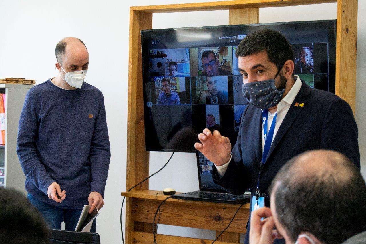 Chakir el Homrani parla amb l'equip del TEB Vist de la sala i també amb les persones que estan connectades per videoconferència a través d'una pantalla gran.