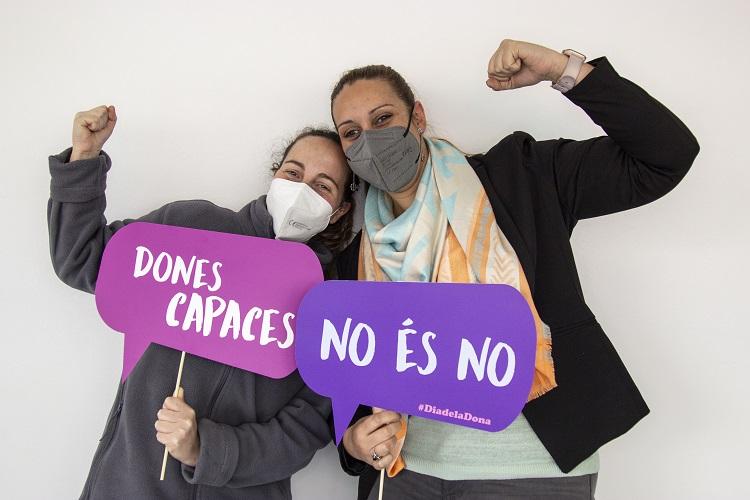 """Apareixen dues dones amb dos rètols lila: """"Dones Capaces"""" i """"No és no"""""""